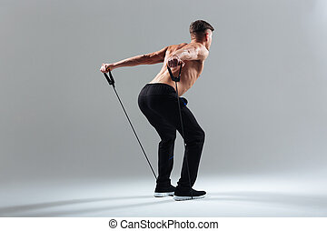 Fitness man workout with expander - Rear view portrait of a...