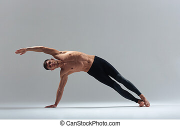 Fitness man doing stretching exercise over gray background