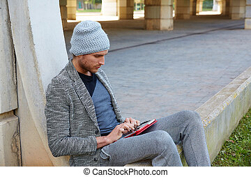 Modern young man with tablet pc under a bridge