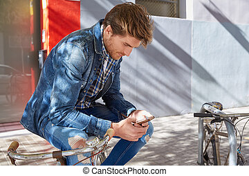 Young man using smartphone in a bicycle with jeans denim...
