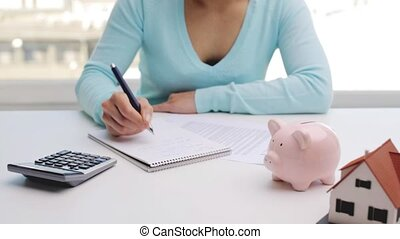 woman counting on calculator and taking notes - business,...
