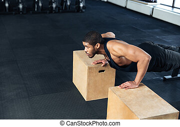 Young Healthy Athlete Doing Push Ups at the gym - Young...