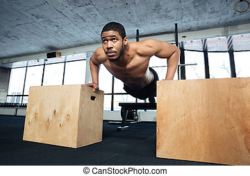 Healthy fitness man doing push-ups in the gym using sports...