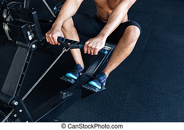 Muscular fitness man using rowing machine in the gym -...
