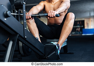 Muscular fitness man using rowing machine - Cropped image of...