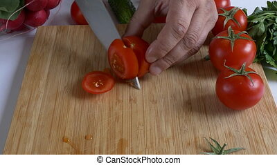 Man's hands chopping tomato