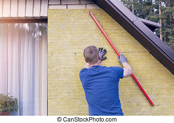 construction worker checks the level of insulated house wall