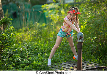 Little girl near the water pump