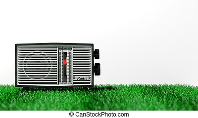 Antique radio transistor on grass, on white background with...
