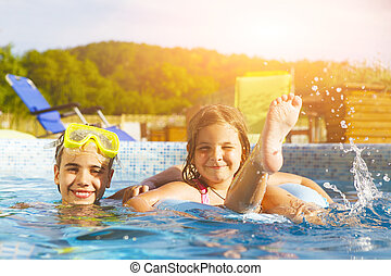 Children playing in pool Two little girls having fun in the...