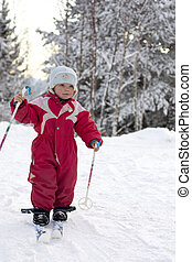 Happy toddler 2 years old skiing in a beautiful winter...