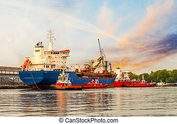 Cargo Ship with Tugboats - Tugboats maneuver a cargo ship in...