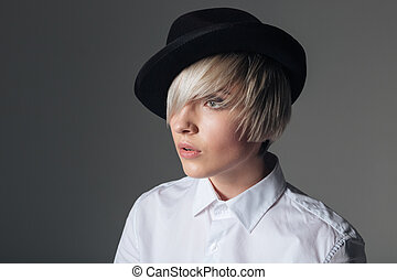Fashion woman in hat looking away over gray background