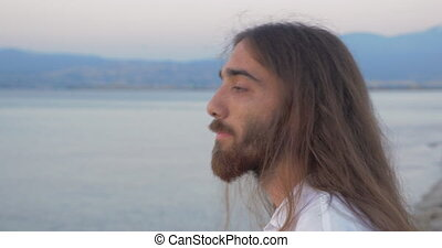 Long-haired man with beard looking to the camera - Close-up...