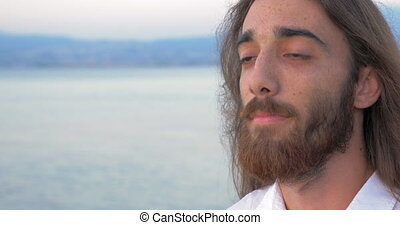 Man with long hair and beard on sea background - Close-up...