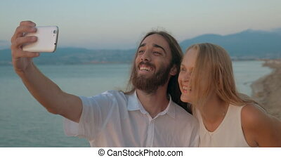 Man and woman posing for selfie on the beach