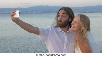 Friends making happy and positive selfie on the beach