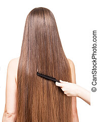 Barbers hand combing her long straight hair on white -...