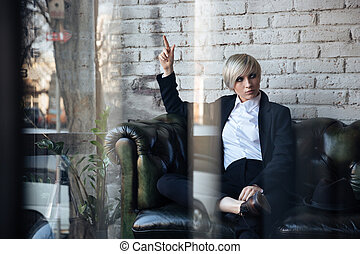 Stylish blonde girl pointing finger at something in a cafe