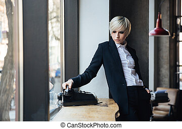 Beautiful stylish girl talking on the phone in cafe -...