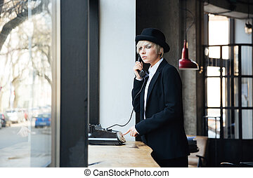Stylish beautiful girl using telephone in cafe - Stylish...