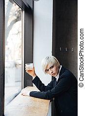 Stylish beautiful blonde drinking at the windowsill -...
