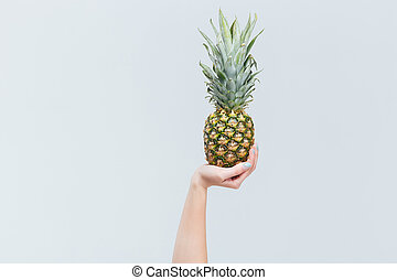 Female hand holding ananas isolated on a white background