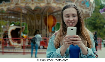 Girl with the phone against the backdrop of a theme park