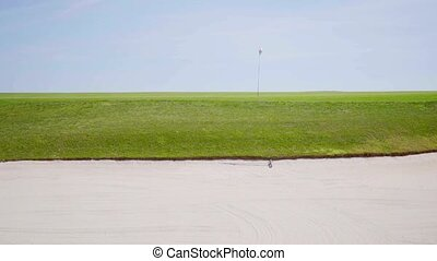 View from the sand bunker on a golf course looking across...
