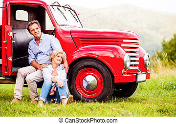 Senior couple sitting at the red vintage car, green sunny...