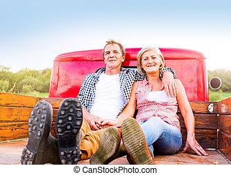 Senior couple sitting in back of red pickup truck - Senior...