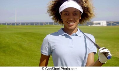 Cheerful female golfer walking with golf club - Single...