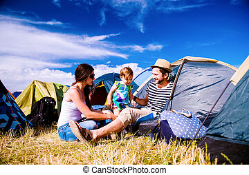 Young couple with their baby daughter in tent, summer -...