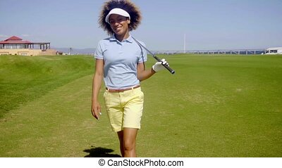 Smiling happy woman golfer walking on the course approaching...