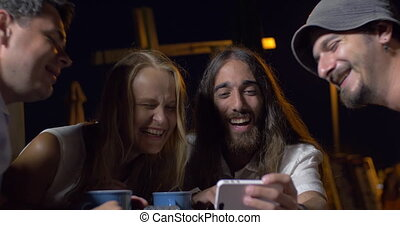 Friends laughing at photos on mobile phone - Four friends...