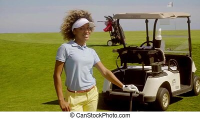Young woman golfer watching her ball on the course - Young...