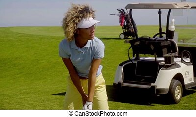 Woman golfer preparing to play a stroke with a golf cart...