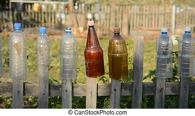 Plastic bottle with the bottom cut off on the old fence