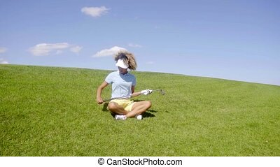 Young woman golfer sitting in the fairway - Young woman...