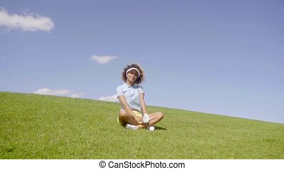 Jaunty young woman golfer sitting on the green