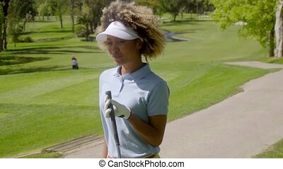 Young woman player walking with a golf club - Young woman...