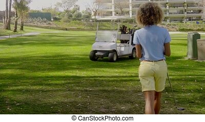 Woman golfer walking back to the golf cart parked on the...