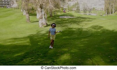 Young female golfer walking across the golf course in the...