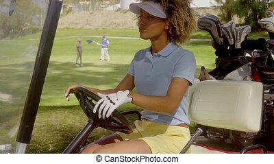 Young woman golfer driving a golf cart with three players...