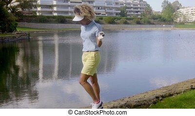 Woman golfer walking beside a lake or water hazard on the...