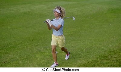 Pretty young woman golfer strolling on the course - Pretty...