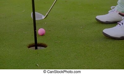 Golfer putting the ball into the hole