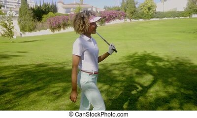 Smiling golfer walking along with a club in hand