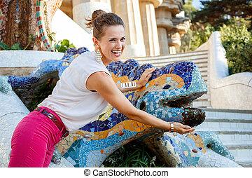 sonriente, mujer, cerca, mosaico, dragón, en, parque,...