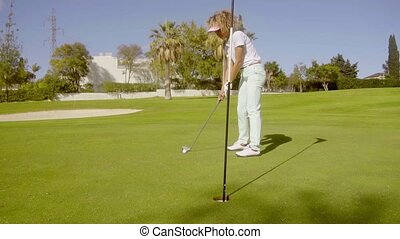 Young woman golfer preparing to sink her putt lining up the...